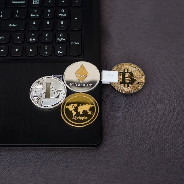 Ein USB-Stick in Bitcoin form steckt in einem Laptop.
